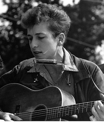 A young Bob Dylan singing protest songs at a rally in the US.